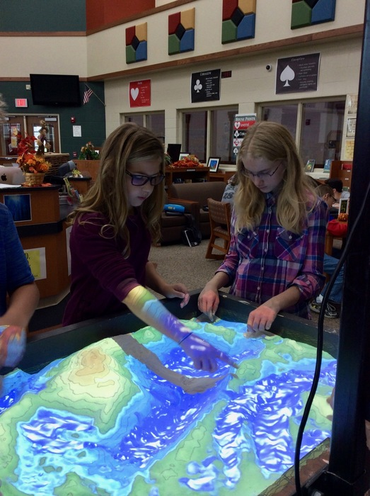 Science 7 students discuss the boundary of the watershed they created in the virtual sandbox.